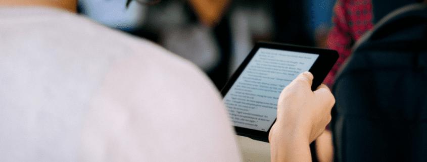 Como funciona uma biblioteca digital: fotografia de uma pessoa lendo um livro digital.