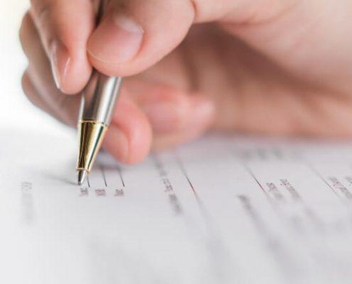 Enade 2020: fotográfia muito próxima de uma pessoa segurando uma caneta e fazendo uma prova.