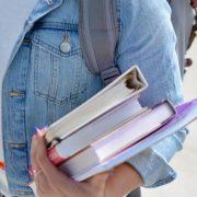 Retenção de alunos no ensino superior: fotografia de uma estudante segurando livros.