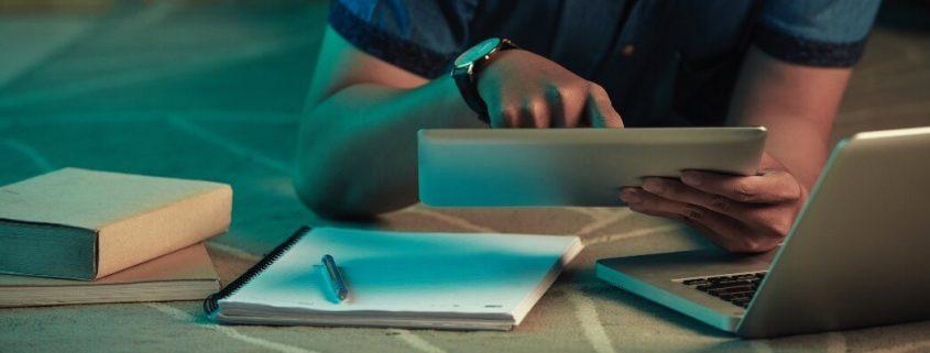 Biblioteca digital: fotografia de um estudante estudando lendo por meio de um tablet e estudando.