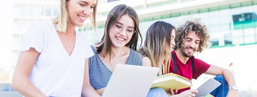 Captação de alunos: fotografia de estudantes conversando e utilizando o computador.