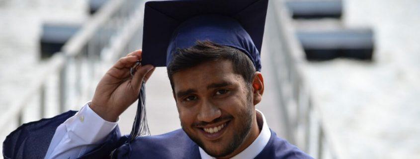 Conceito Preliminar de Curso: fotografia de um formando universitário segurando o seu capelo.