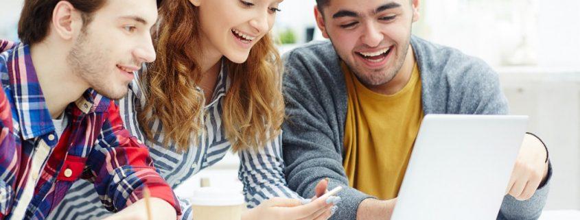 Ferramentas de metodologias ativas: fotografia de três estudantes universitários usando o computador.