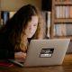 Tecnologia no ensino: fotografia de uma mulher usando o computador em uma biblioteca.