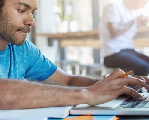 Banco de questões Enade: fotografia de um estudante usando um notebook.