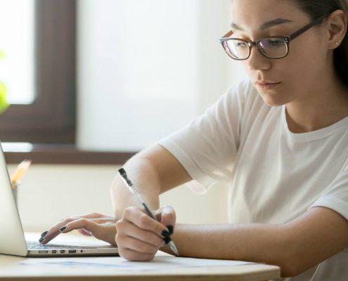 Biblioteca universitária online: fotografia de uma estudante lendo pelo computador.