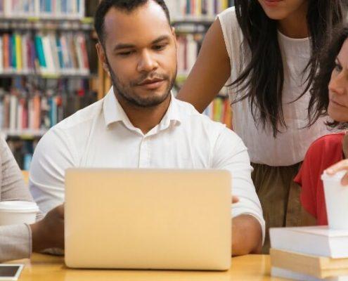 Como organizar biblioteca: fotografia de 4 bibliotecários utilizando o notebook em uma biblioteca.