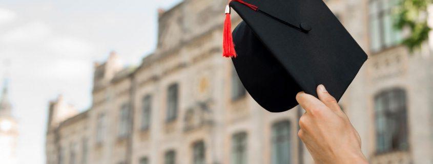 Conceito Enade: fotografia de um estudante segurando um capelo em frente a uma universidade.