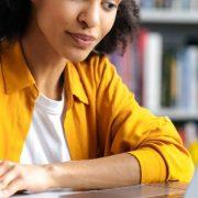 Simulado Enade: fotografia de uma estudante olhando para a tela do computador e anotando em um caderno.