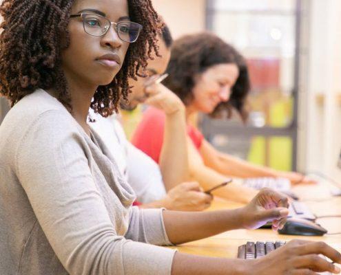 Como funciona graduação a distância: fotografia de pessoas estudando pelo computador.