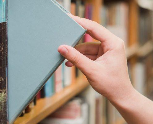 Como incentivar a leitura: fotografia com foco em uma mão de uma pessoa retirando um livro de uma estante.