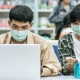 Educação pós-pandemia: fotografia de dois estudantes usando máscaras em uma biblioteca.
