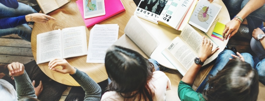 Metodologias ativas no ensino superior: fotografia de uma mesa com diversos alunos reunidos estudando.