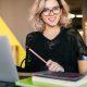 Plataforma digital de aprendizagem: fotografia de uma estudante sorrindo para a câmera. Ela está estudando pelo computador e conta com alguns livros a sua frente.