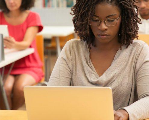 Saraiva Educação: fotografia com foco em uma estudante utilizando o notebook.