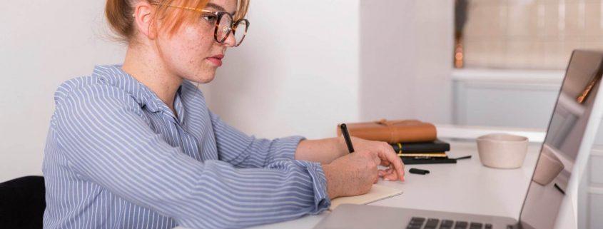 Como montar um curso EaD: fotografia de uma estudante fazendo aula online, utilizando o notebook.