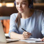 Carga horária curso EaD: fotografia de uma estudante assistindo aula online e fazendo anotações.