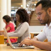 Edital Enade: fotografia com foco em um homem utilizando um computador em uma biblioteca.
