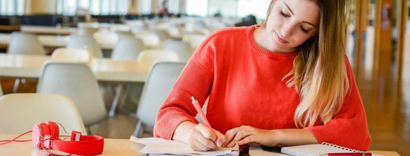 Indicadores de qualidade do MEC: fotografia de uma estudante escrevendo em um caderno.