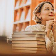 Ranking Enade: fotografia de uma mulher em uma biblioteca, apoiada em uma mesa e olhando para cima.