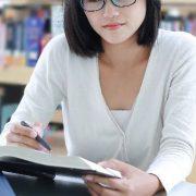Carga horária do curso de Direito: fotografia de uma estudante lendo um livro em uma biblioteca.