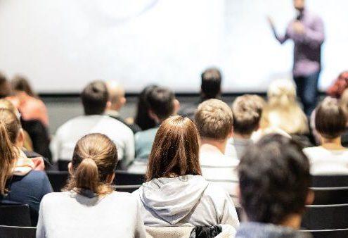Desafios da educação: fotografia de um auditório lotado. Uma pessoa está palestrando e há diversos alunos assistindo.