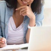 Ensino híbrido, desafios e oportunidades: fotografia de uma mulher estudando pelo notebook e sorrindo.