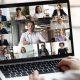 Ensino híbrido na prática: fotografia de uma pessoa participando de uma videoconferência. Foco na tela do computador, com várias pessoas.
