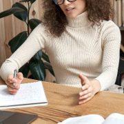 Ensino híbrido no ensino superior: fotografia de uma estudante participando de uma aula online e fazendo anotações.
