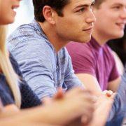 Ensino por competências na educação profissional: fotografia de estudantes sentados à mesa e prestando atenção a uma aula.