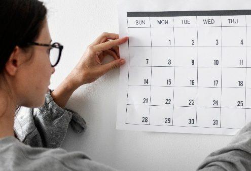 Calendário ensino superior: fotografia de uma mulher colocando um calendário em uma parede.
