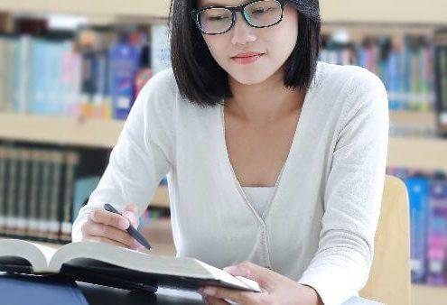Diretrizes Curriculares do Curso de Direito: fotografia de uma estudante lendo um livro e fazendo anotações. Ela está sentada e atrás está uma estante de livros.