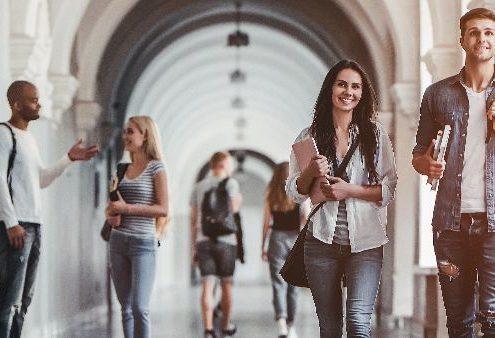 Estratégias para captação de alunos: fotografia de alunos caminhando e conversando em um corredor de uma universidade.