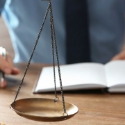 Fontes do Direito: fotografia com foco na balança da justiça. Ao fundo, uma pessoa está analisando um livro e outra está apontando para uma das páginas.