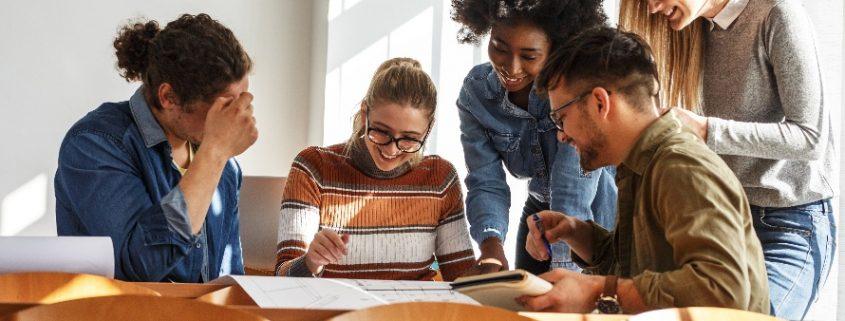 Inovação curricular no ensino superior: fotografia de um grupo de estudantes sorrindo enquanto realizam um trabalho.