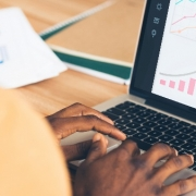 Learning Analytics: fotografia de uma pessoa utilizando um notebook. No notebook, aparecem diversos gráficos.