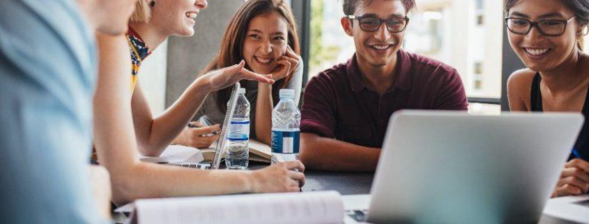 O que é EaD, semipresencial e presencial: fotografia de um grupo de 5 estudantes sorrindo e estudando. Na mesa, há garrafas de água, livros e notebook.