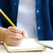Tipos de EaD: fotografia com foco em um estudante utilizando o computador para assistir aulas e fazendo anotações em um caderno.