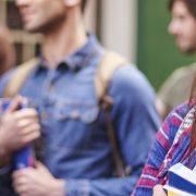 Fotografia com foco em uma estudante segurando um livro e sorrindo.