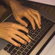Inteligência educacional: fotografia com foco nas mãos de uma pessoa digitando em um computador.