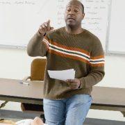 Liderança inovadora: fotografia de um professor à frente de uma sala de aula apontando para um estudante que está com o braço levantado para fazer uma pergunta.