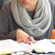 Livros sobre metodologias ativas: fotografia de uma pessoa lendo um livro e fazendo anotações em um caderno.