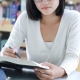 Selo OAB Recomenda: fotografia de uma estudante lendo na biblioteca.
