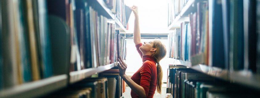 Catalogação de livros: fotografia de uma mulher organizando os livros nas estantes de uma biblioteca.