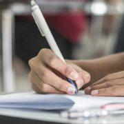 Enade: fotografia de uma estudante fazendo uma prova em uma sala de aula.