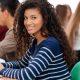 Nota do MEC: fotografia de uma sala de aula com foco em uma mulher sorrindo.