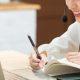 Fotografia de uma mulher sorrindo e anotando enquanto faz aulas online.