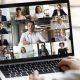 Como montar um curso de pós-graduação: fotografia de uma pessoa participando de uma aula online. Na tela do computador, estão aparecendo várias pessoas em uma reunião virtual.