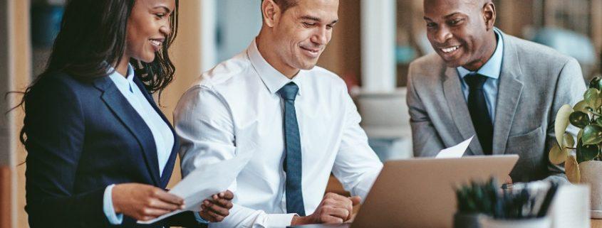 O futuro do profissional do Direito: três profissionais sorrindo e usando o computador