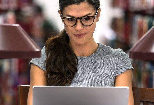 Perfil dos alunos do curso de Direito: conheça as características: mulher estudando em biblioteca